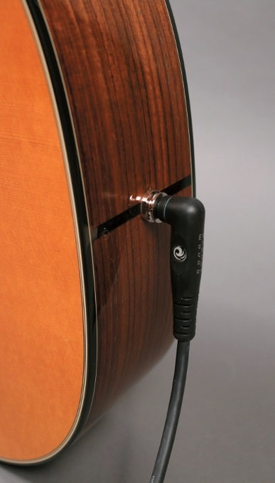 Most acoustic pickup systems offer an endpin jack, i.e. the combination of an output socket and a belt holding button.
